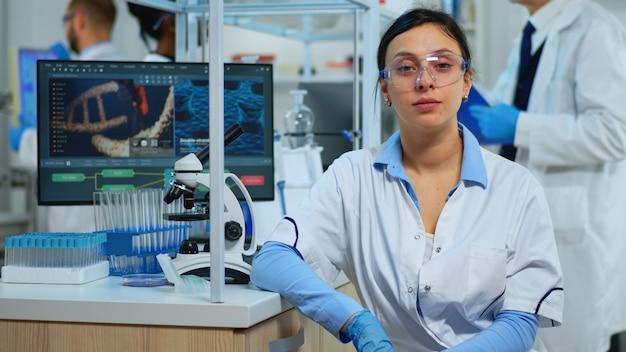 Retrato de cientista sorrindo para a câmera, sentado no moderno laboratório equipado. equipe multiétnica examinando a evolução do vírus usando ferramentas de alta tecnologia e química para pesquisa científica, desenvolvimento de vacinas