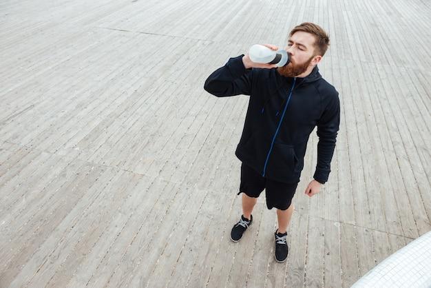 Retrato de cima da imagem de corpo inteiro do corredor beber água