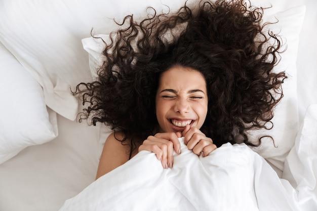 Retrato de cima de uma mulher alegre de 20 anos com cabelo escuro e encaracolado franzindo os olhos, deitada na cama sob um cobertor branco com um sorriso feliz