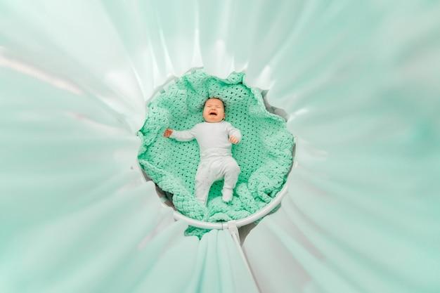 Retrato de cima do lindo bebê recém-nascido chorando, deitado de costas na cama redonda branca com dossel de esmeralda. creche para criança. as crianças dormem com roupas. encantadora criança alegre rastejando e fazer caretas.