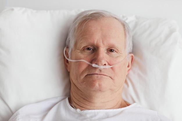 Retrato de cima para baixo de um homem sênior deitado em uma cama de hospital com suplementação de oxigênio e olhando para a câmera, copie o espaço