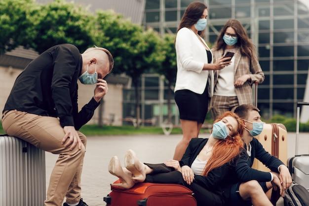 Retrato de cinco amigos esperando o voo, sentado no asfalto, usando telefones celulares