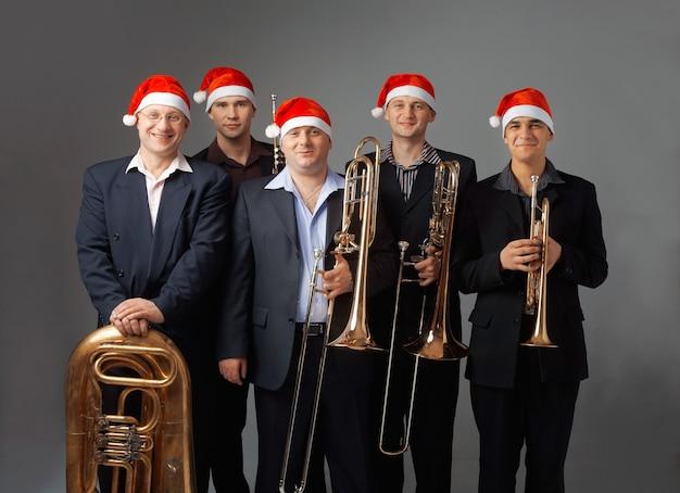 Retrato de cinco jovens músicos com instrumentos. eles estão vestidos com um boné de papai noel