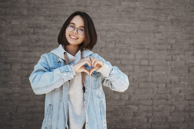 Retrato de cintura de mulher do lado de fora em um dia ensolarado de primavera, sobre a parede do prédio de tijolos, sorrindo feliz câmera, mostre o sinal do coração sobre o peito para expressar amor, cuidado e simpatia.
