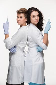 Retrato de cirurgiões de duas mulheres mostrando seringas
