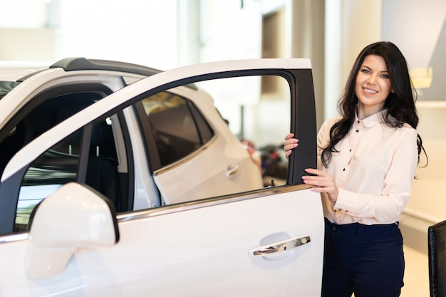 Retrato de cliente feliz comprando carro novo e examina o carro