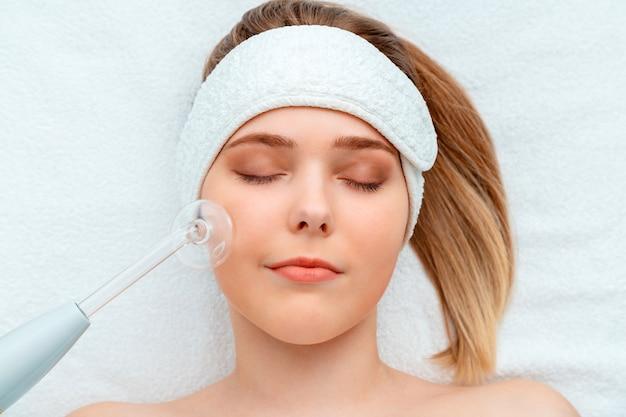 Retrato de cliente mulher durante o procedimento de cosmetologia darsonval para a saúde dos cuidados da pele encontra-se na toalha branca. dispositivo de cosméticos e esteticista para spa de cuidados com a pele do rosto, cabelo e corpo.