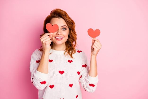 Retrato de close-up agradável atraente muito fofo encantadora alegre garota segurando na mão um pequeno coração fechando os olhos se divertindo