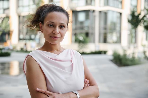Retrato de close-up confiante de uma mulher de negócios de meia-idade bem-sucedida em traje casual, posando para a câmera com aríetes cruzados no fundo de edifícios altos