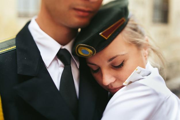 Retrato de close-up da noiva sobre os ombros de homens militares