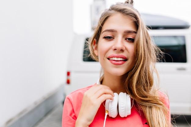 Retrato de close-up de adorável menina loira andando na rua com grandes fones de ouvido brancos