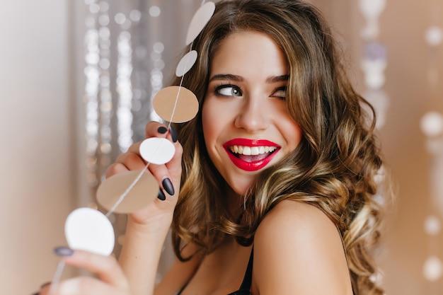 Retrato de close-up de adorável mulher de olhos azuis divertidamente olhando para longe com a boca aberta. fascinante garota branca com cabelo brilhante, posando na parede brilhante.