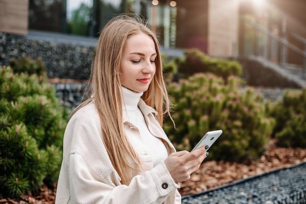 Retrato de close-up de aluna loira sorrindo e usando telefone celular, enviando mensagens de texto, digitando e lendo mensagem contra o prédio da faculdade