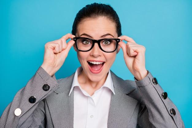Retrato de close-up de atraente inteligente inteligente alegre senhora tocando especificações isoladas sobre fundo de cor azul vibrante
