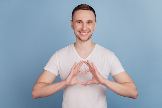 Retrato de close-up de cara feliz sorrindo, mostrando a figura de um coração amor romântico isolado sobre fundo azul