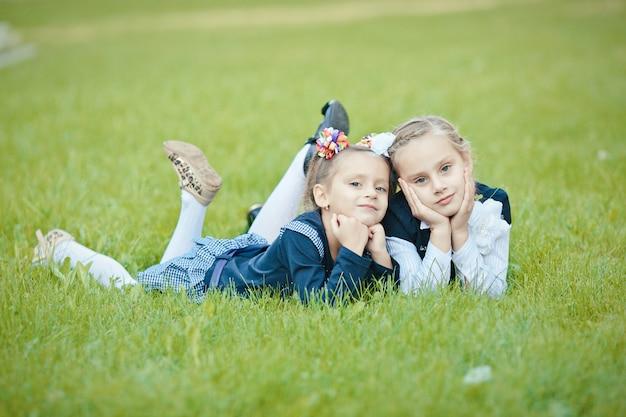 Retrato de close-up de duas simpáticas irmãs atraentes cativantes adoráveis fofas simpáticas alegres deitadas na grama verde ao ar livre, passando o fim de semana de férias olhando para a câmera