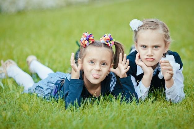 Retrato de close-up de duas simpáticas irmãs atraentes cativantes adorável fofas amigáveis alegres deitadas na grama verde ar fresco passando férias feriado fim de semana fazendo careta e brincar ao ar livre
