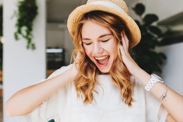 Retrato de close-up de garota encaracolada em êxtase usando pulseira da moda e relógio de pulso rindo com os olhos fechados