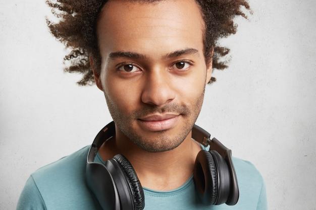 Retrato de close up de homem pardo de pele escura com olhos escuros e eriçados, tem fones de ouvido