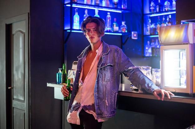 Retrato de close-up de jovem com uma jaqueta jeans e cerveja no bar