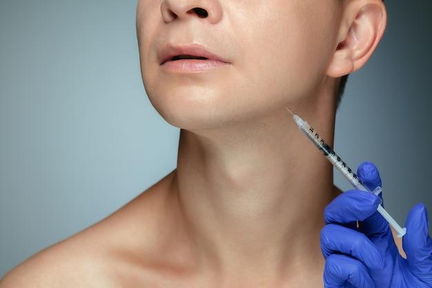 Retrato de close-up de jovem isolado na parede cinza do estúdio em procedimento de cirurgia de enchimento