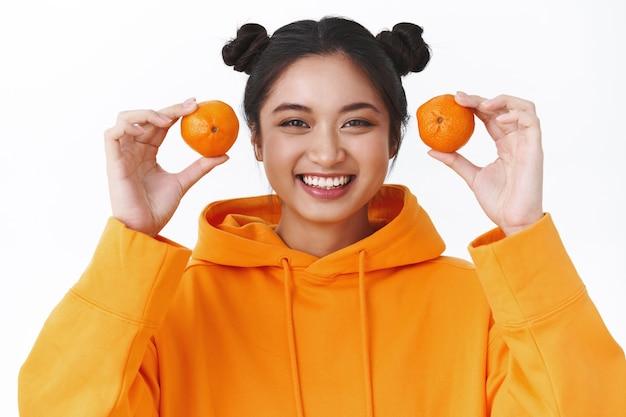 Retrato de close-up de kawaii sorrindo jovem asiática com duas tangerinas, dando uma risadinha boba e olhando a câmera, comendo frutas, brincando com tangerinas, brincando infantil, parede branca