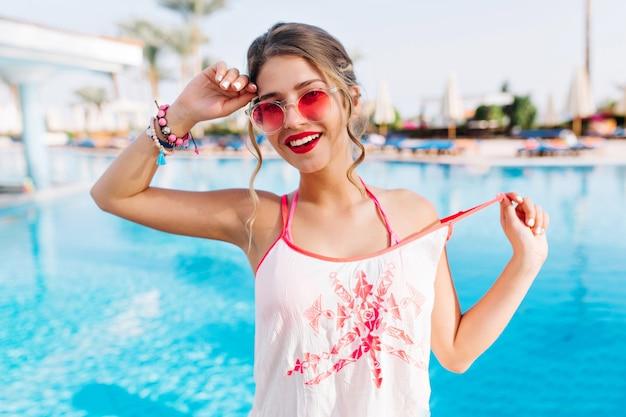 Retrato de close-up de linda garota bronzeada em óculos de sol rosa, posando com as mãos para cima e expressão de rosto feliz