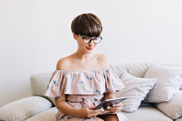 Retrato de close-up de menina bonita com penteado curto usando novo gadget sentado no sofá em casa