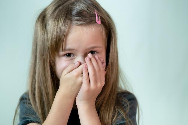 Retrato de close-up de menina criança com cabelos longos, cobrindo a boca com as mãos.