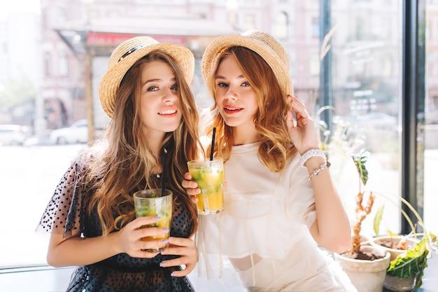 Retrato de close-up de meninas cansadas, mas felizes, tomando coquetéis depois das compras no fim de semana