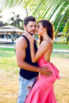 Retrato de close-up de moda solar ao ar livre de um lindo casal em uma diversão animada em um dia de verão na natureza exótica. desfrutar, amar, experimentar alegria. moda casal abraços e beijos.