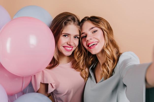 Retrato de close-up de mulher animada com cabelo encaracolado fazendo selfie com uma amiga