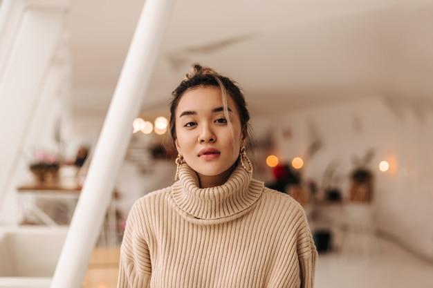 Retrato de close-up de mulher asiática de olhos castanhos, vestindo um suéter bege de gola alta, olhando para a frente