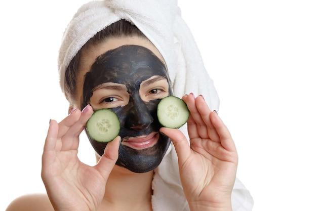 Retrato de close-up de mulher bonita com máscara facial preta e fatias de pepino nas mãos sobre fundo branco