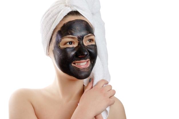 Retrato de close-up de mulher bonita com máscara facial preta em branco, menina com uma toalha branca na cabeça