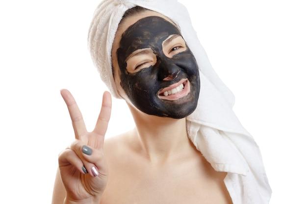 Retrato de close-up de mulher bonita com máscara facial preta em fundo branco, garota com uma toalha branca na cabeça