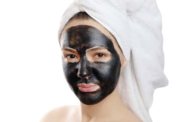 Retrato de close-up de mulher bonita com máscara facial preta em fundo branco