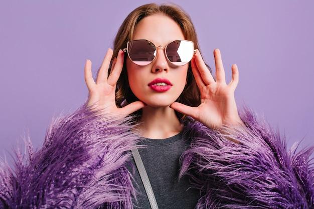 Retrato de close-up de mulher com lábios rosados olhando através de elegantes óculos de sol