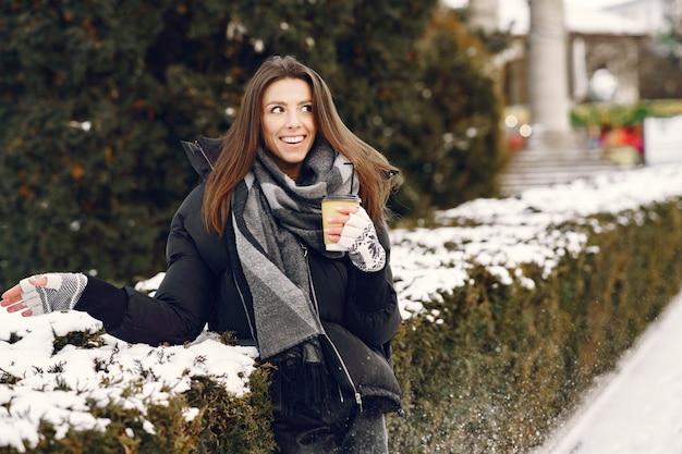 Retrato de close-up de mulher de jaqueta preta bebendo café