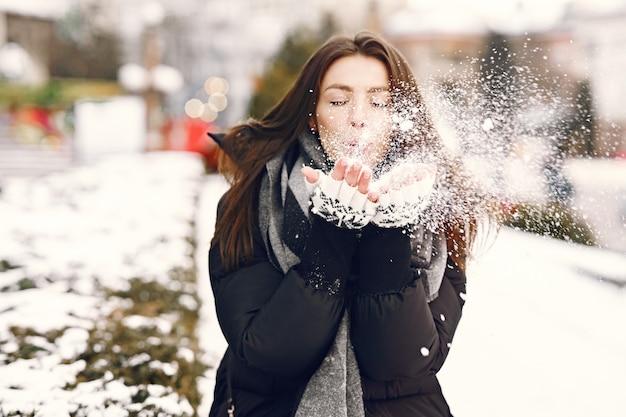 Retrato de close-up de mulher de jaqueta preta brincando com a neve