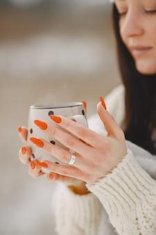 Retrato de close-up de mulher de suéter branco com chá