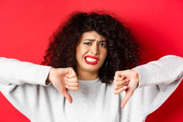 Retrato de close-up de mulher desapontada fazendo careta, encolhendo-se de algo ruim, mostrando o polegar para baixo, desgosto e desaprovação, em pé na parede vermelha.
