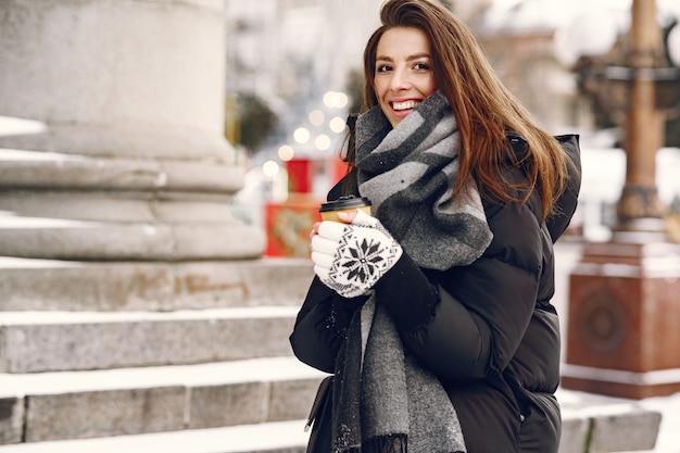 Retrato de close-up de mulher em jaqueta preta com café para viagem