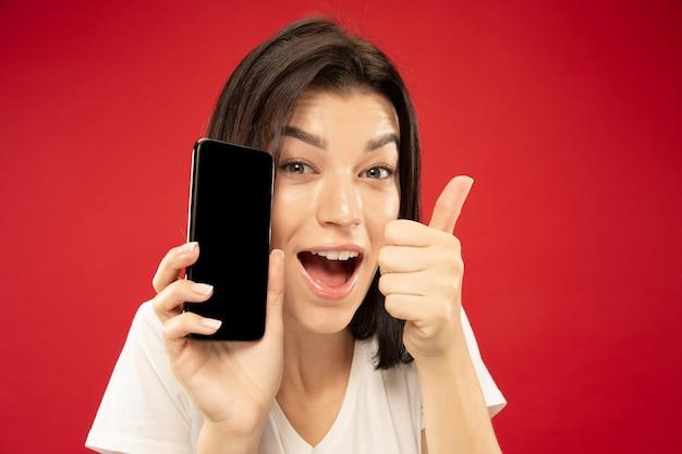 Retrato de close up de mulher jovem caucasiana no fundo vermelho do estúdio. bela modelo feminino em camisa branca. conceito de emoções humanas, expressão facial, vendas. segurando o telefone, parece feliz, mostra-se bem.