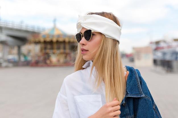 Retrato de close-up de mulher jovem e atraente elegante com cabelos loiros, vestida de blusa branca e xale no cabelo com óculos pretos, posando na cidade