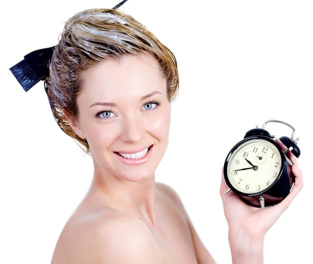 Retrato de close-up de mulher jovem e bonita com sorriso atraente, pintando o cabelo e segurando o alarme - isolado