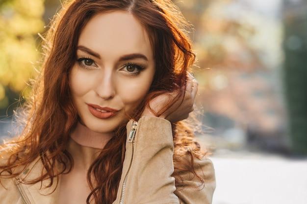 Retrato de close-up de mulher jovem e sensual brincando com seu cabelo ruivo escuro