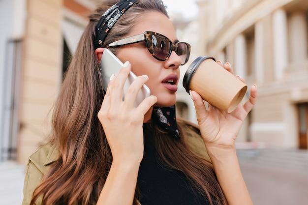 Retrato de close-up de mulher latina ocupada falando no telefone e segurando uma xícara de chá