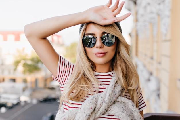 Retrato de close-up de mulher levemente bronzeada cobrindo a testa com a mão e sorrindo suavemente no desfoque de fundo da cidade