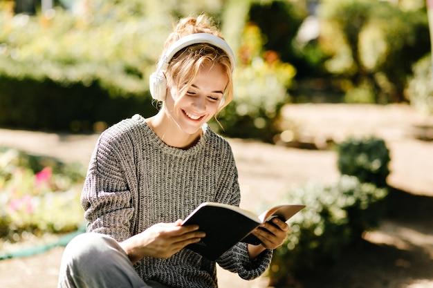 Retrato de close-up de mulher ouvindo música e lendo um livro